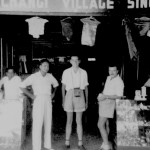 Roy Parsons (With Camera) Standing in a Changi Village Shop.